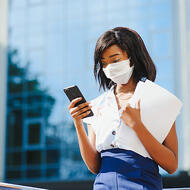 Insurance agent in a mask looking at her phone-square